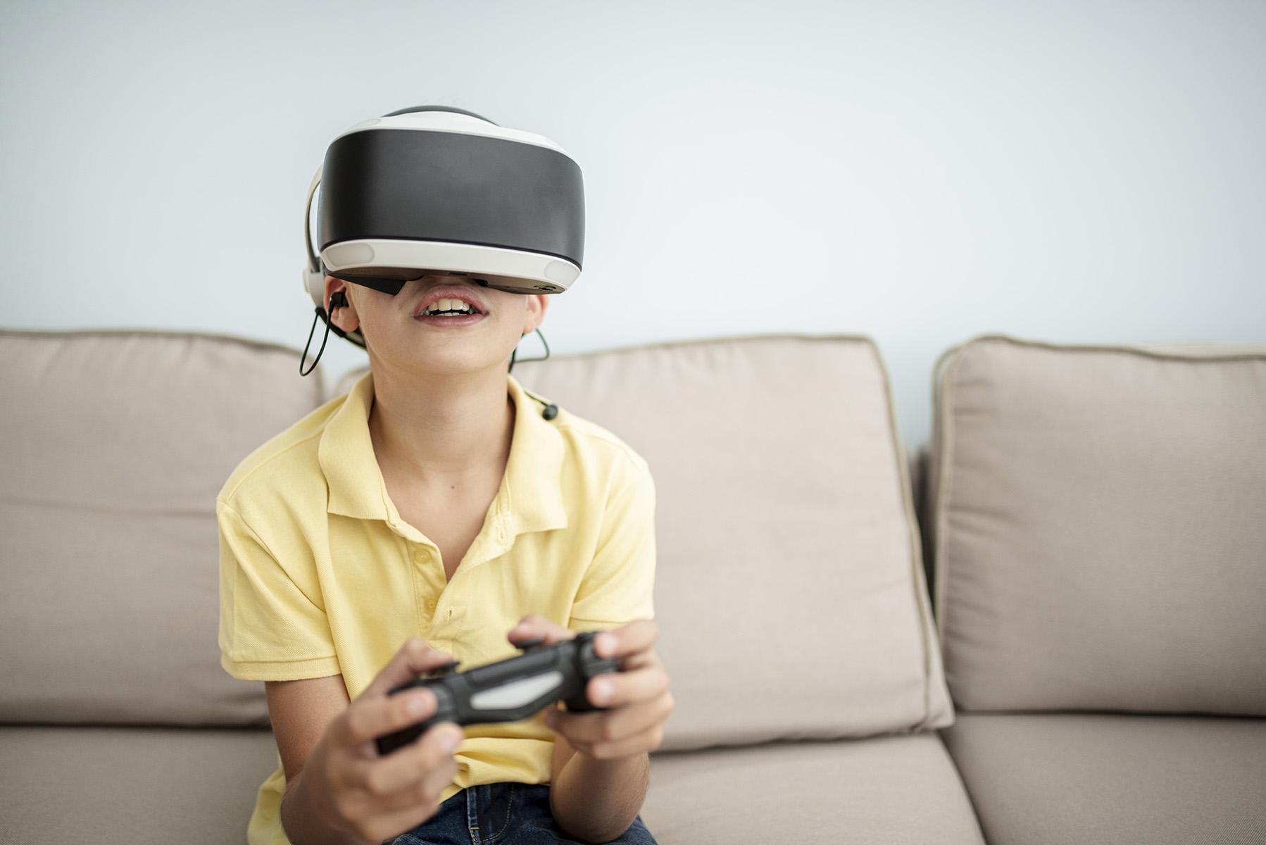 Menino sorridente joga videogame na sala de casa